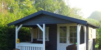 graues gartenhaus mit weißer veranda von steda