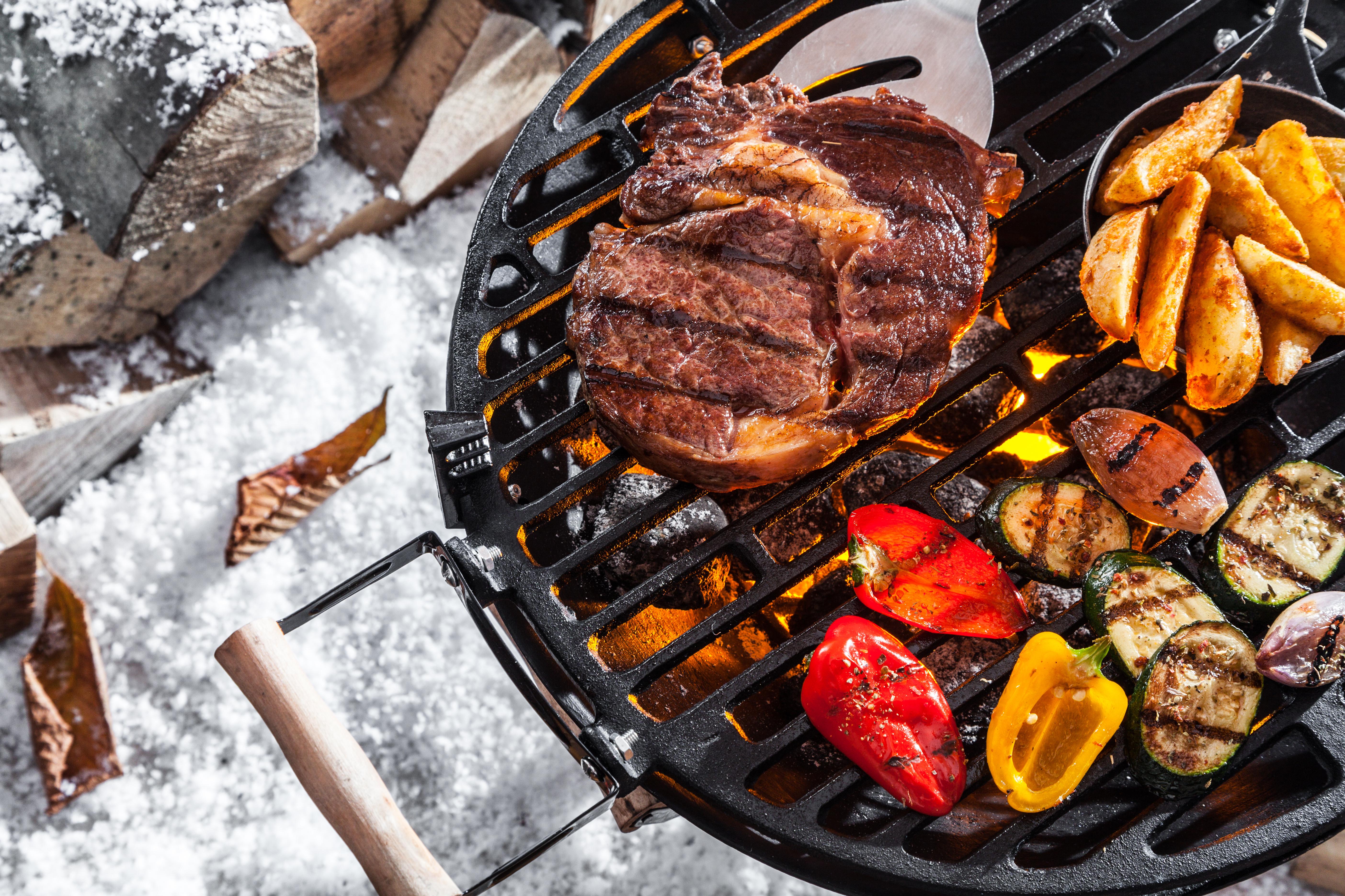 Grillen im Winter mit einem Grill mit Fleisch und Gemüse auf Schnee