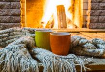 gemütlicher Abend vor einem Kamin im gartenhaus mit zwei Tassen vor dem Feuer