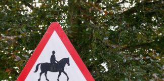 Achtung Pferde Schild vor einem Baum