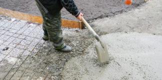 Arbeiter beim Verlegen eines Fundaments für ein Gartenhaus