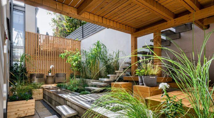 Erhöhte-Holzterrasse-grüne-Pflanzen-mit-Wasserbrunnen