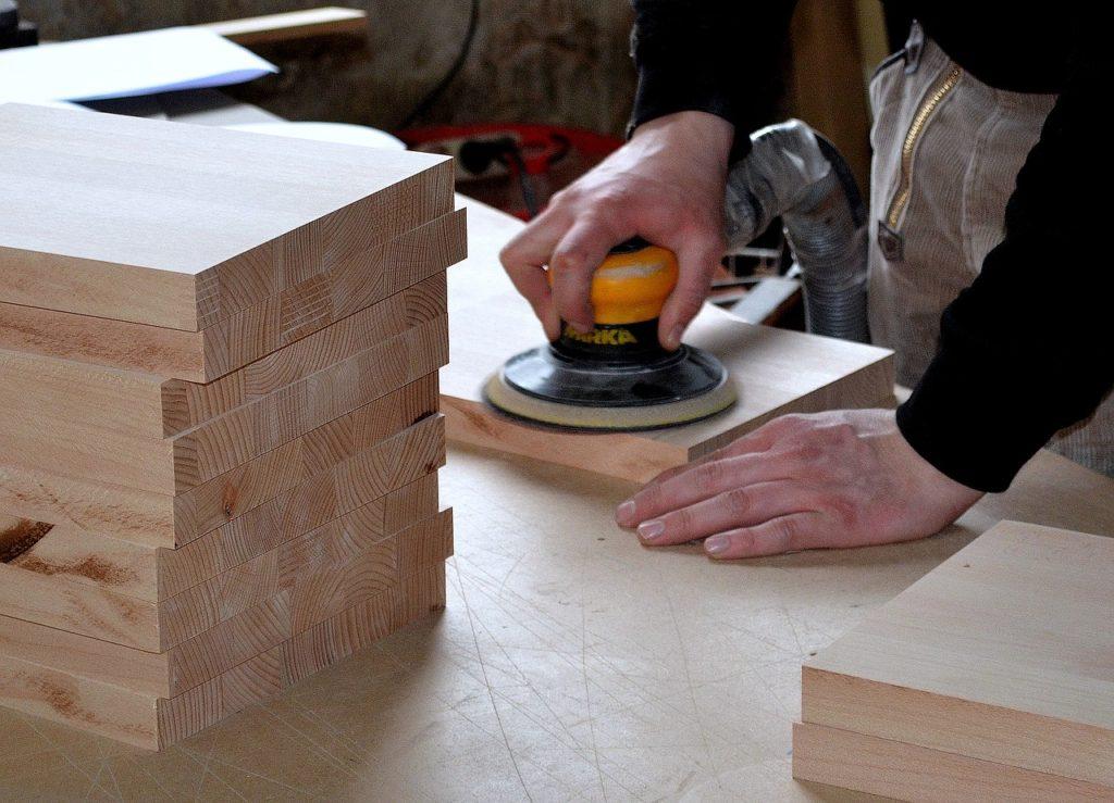 Mann-schleift-Holz-mit-Schleifmaschine