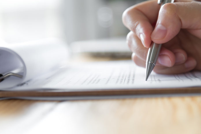 versicherung für eine terrassenüberdachung - mann unterschreibt vertrag