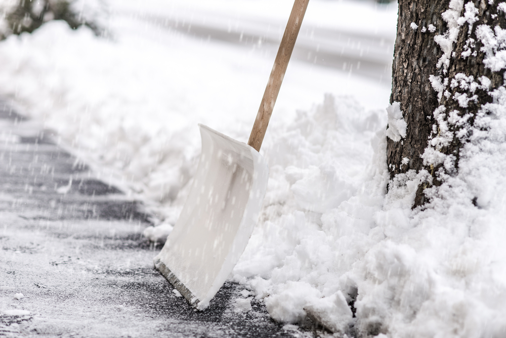 Schnee an einer Straße mit einer Schneeschaufel