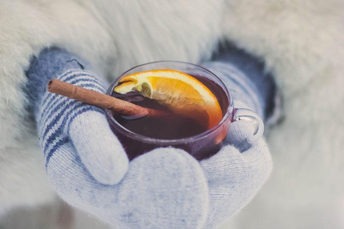 Hände halten Glühweinbecher miz Handschuhen