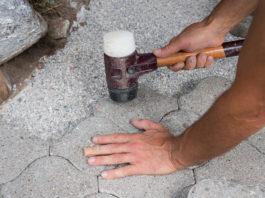 durch Klopfen auf Pflastersteine wird Fundament gefestigt