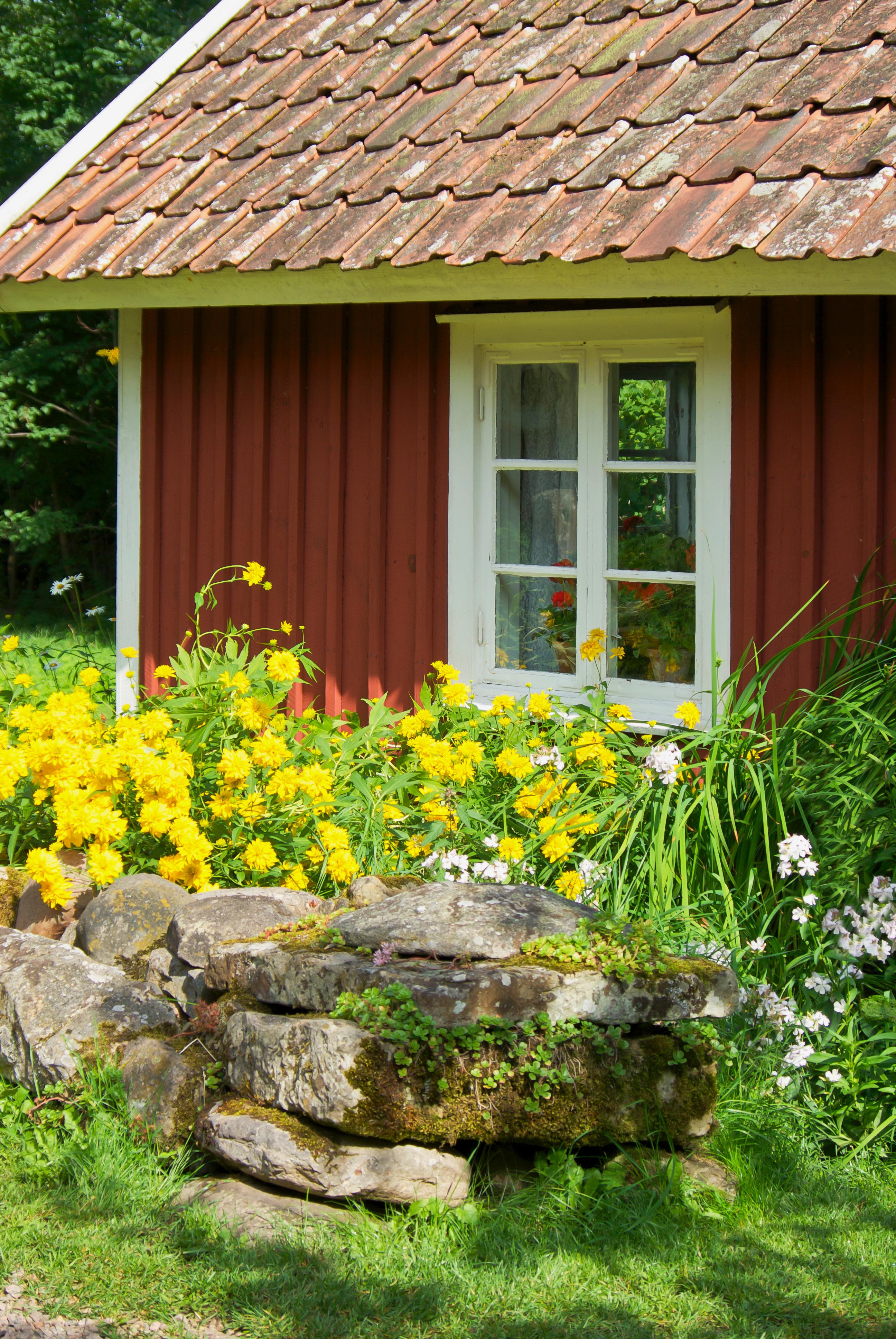 Steinbeet mit haus in schwedenrot
